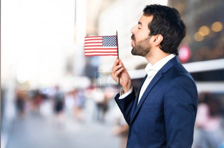Handsome man holding an american flag on unfocused background