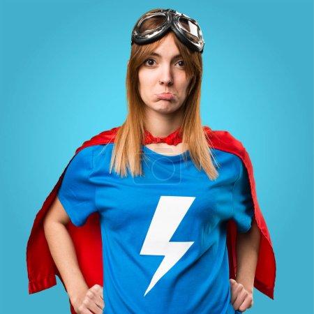 Sad pretty superhero girl on colorful background