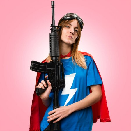 Pretty superhero girl holding a rifle on colorful background
