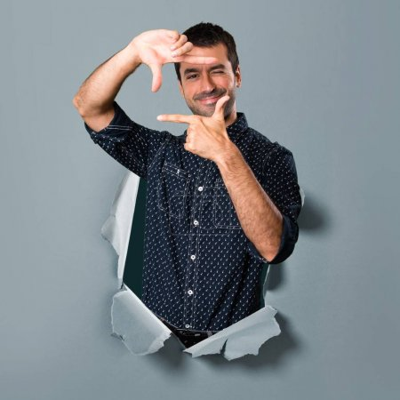 Brunette man focusing with his fingers through a paper hole
