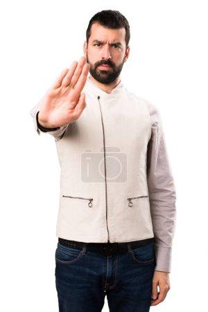 Photo pour Bel homme avec gilet faisant signe de stop sur fond blanc isolé - image libre de droit