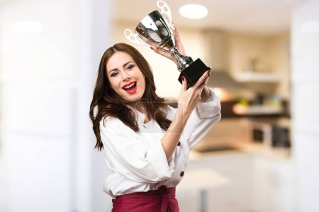 Beautiful chef woman holding a trophy on unfocused background