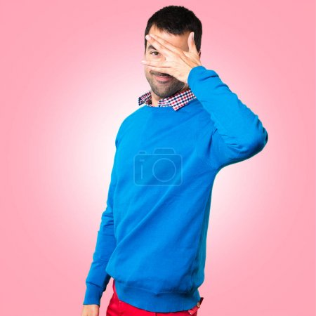 Handsome young man covering his eyes on colorful background