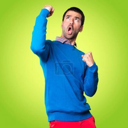 Photo pour Chanceux beau jeune homme sur fond coloré - image libre de droit