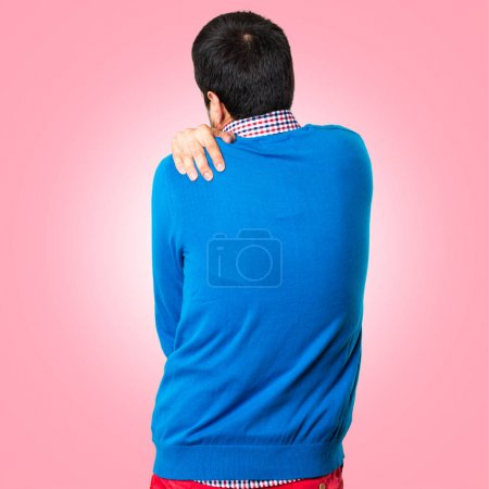 Handsome young man with shoulder pain on colorful background