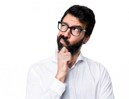 Photo pour Bel homme avec des lunettes pensant - image libre de droit