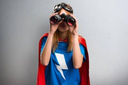 Pretty superhero girl with binoculars on a gray textured background