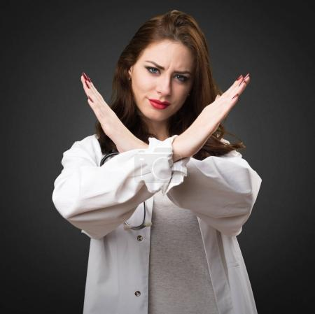 Doctor woman making NO gesture on black background