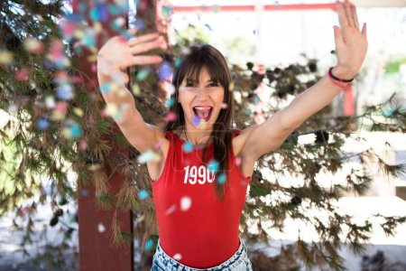 Beautiful young girl playing with confetti