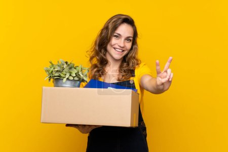 Photo pour Young blonde girl making a move while picking up a box full of things smiling and showing victory sign - image libre de droit