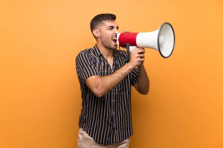 Photo for Handsome man with beard over isolated background shouting through a megaphone - Royalty Free Image