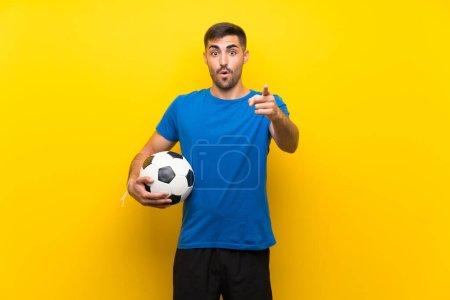 Photo pour Jeune joueur de football sur un mur jaune isolé surpris et pointé du doigt - image libre de droit