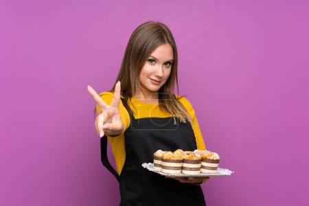Photo pour Jeune adolescente tenant de nombreux petits gâteaux sur un fond violet isolé souriant et montrant un signe de victoire - image libre de droit