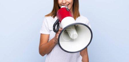 Photo pour Jeune femme au-dessus du fond bleu d'isolement criant par un mégaphone - image libre de droit