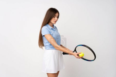 Photo for Young girl over isolated white wall playing tennis - Royalty Free Image