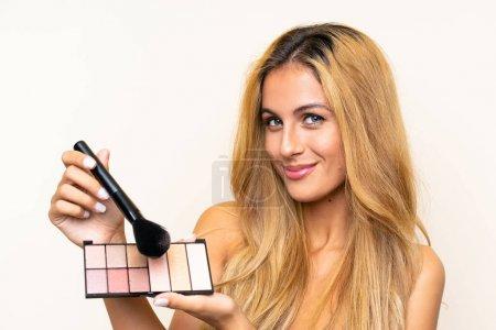 Photo pour Jeune femme blonde avec le remaquillage au-dessus du fond d'isolement - image libre de droit