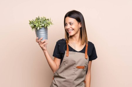 Photo pour Jeune femme tenant une plante avec une expression heureuse - image libre de droit