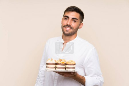 Photo for Handsome man holding muffin cake over isolated background - Royalty Free Image