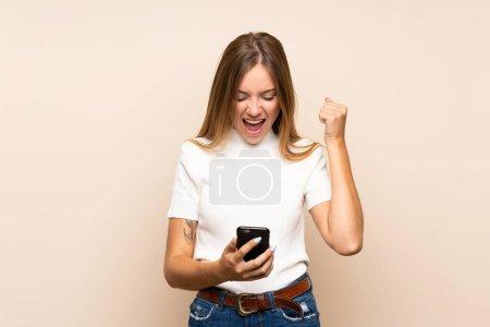 Młoda blondynka na odizolowanym tle za pomocą telefonu komórkowego