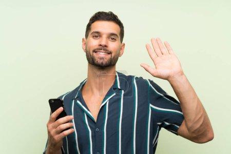 junger gutaussehender Mann mit einem Mobiltelefon, der mit fröhlichem Gesichtsausdruck grüßt
