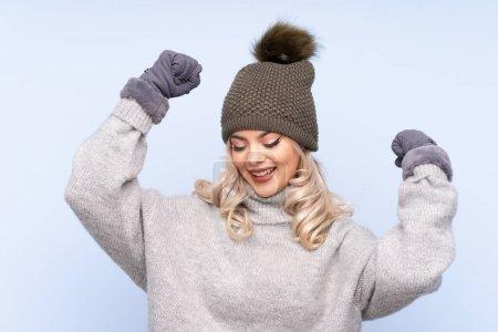 Photo pour Jeune adolescente portant un chapeau d'hiver sur fond bleu isolé célébrant une victoire - image libre de droit