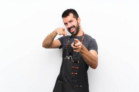 Photo pour Barbier dans un tablier pointe du doigt vers vous tout en souriant - image libre de droit