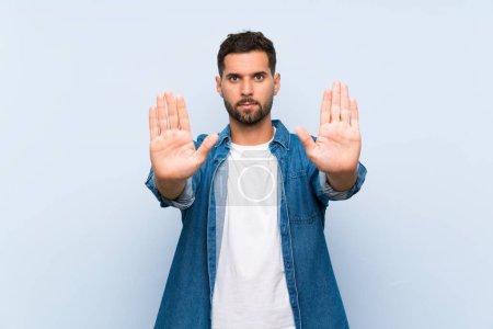 Photo pour Homme bel au-dessus du fond bleu d'isolement faisant le geste d'arrêt et déçu - image libre de droit