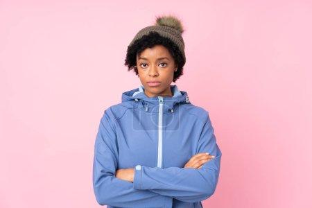 Photo pour Femme africaine-américaine portant un chapeau d'hiver sur fond rose isolé, les bras croisés - image libre de droit