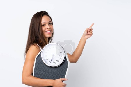 Photo for Young Brazilian girl holding a scale over isolated background with weighing machine and pointing side - Royalty Free Image