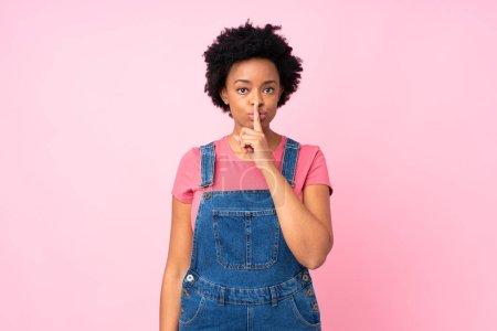 Photo pour Femme afro-américaine avec salopettes sur fond rose isolé faisant geste de silence - image libre de droit