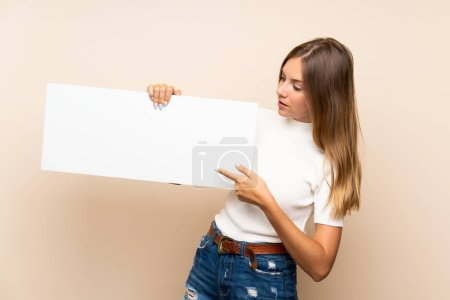 Photo for Young blonde woman over isolated background holding an empty white placard for insert a concept - Royalty Free Image