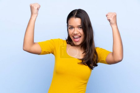 Photo pour Young Colombian girl over isolated blue background celebrating a victory - image libre de droit