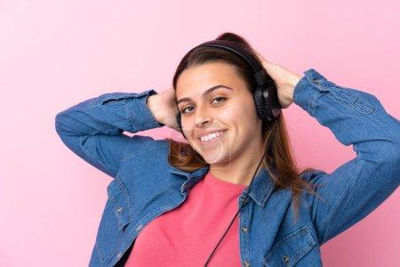 Photo pour Une adolescente écoute de la musique sur un mur rose isolé - image libre de droit
