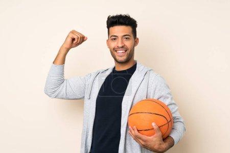 Photo pour Jeune homme beau au-dessus du fond d'isolement avec la bille du basket-ball - image libre de droit
