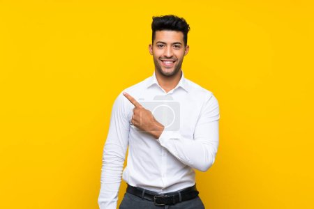 Photo for Young handsome man over isolated yellow background pointing finger to the side - Royalty Free Image