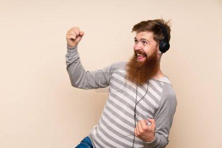 Photo pour Homme à tête rouge avec barbe longue sur fond isolé utilisant le mobile avec écouteurs et danse - image libre de droit