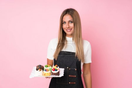 Photo pour Young blonde woman over isolated pink background holding mini cakes - image libre de droit