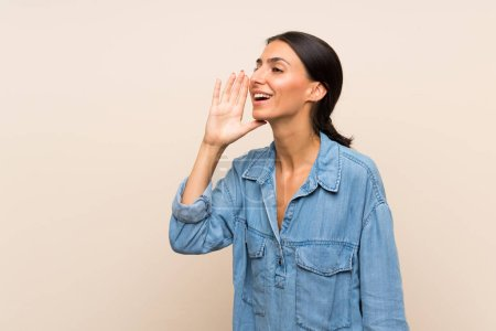 Young woman over isolated background shouting with mouth wide open to the lateral