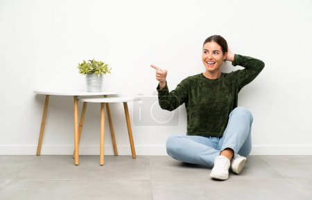 Photo for Young woman sitting on the floor surprised and pointing finger to the side - Royalty Free Image