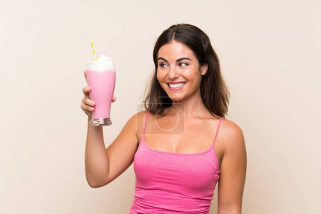 Photo for Young woman with strawberry milkshake with happy expression - Royalty Free Image