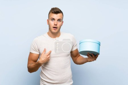 Photo pour Jeune homme blond beau au-dessus de la boîte bleue d'isolement de fixation de fond - image libre de droit
