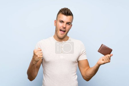 Photo pour Young handsome jolie blonde man over isolated blue background holding a wallet - image libre de droit