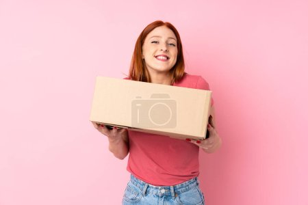 Young redhead woman over isolated pink background ...