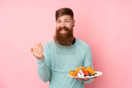 Photo pour Redhead man with long beard holding waffles over isolated pink background inviting to come with hand. Happy that you came - image libre de droit