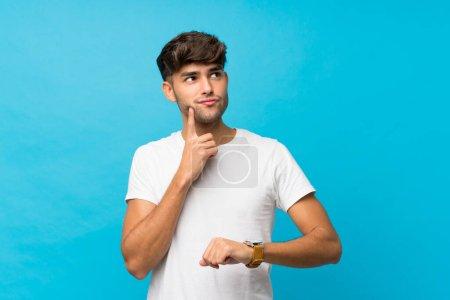 Foto de Joven hombre guapo sobre fondo azul aislado con reloj de muñeca y pensando en una idea. - Imagen libre de derechos