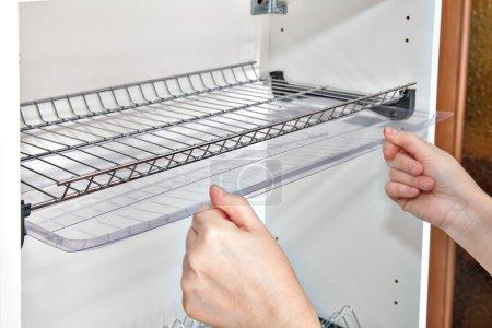 Photo pour Installation étagère dans le placard de la cuisine avec à l'intérieur de fil plaque support, gros plan d'un bac de récupération de cales de mains femme. - image libre de droit
