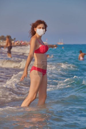 Photo for Young caucasian attractive woman in disposable facial surgical mask as a protection during coronavirus covid-19 pandemic is going to swim in the sea in red swimsuit. Travel and resort season 2020. - Royalty Free Image