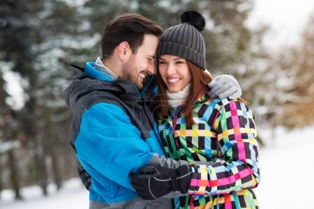 Hugging in forest at snow winter day