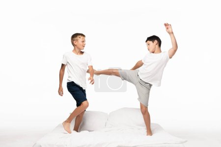 Photo for Boy jokingly kicking brother with leg while having fun on bed isolated on white - Royalty Free Image