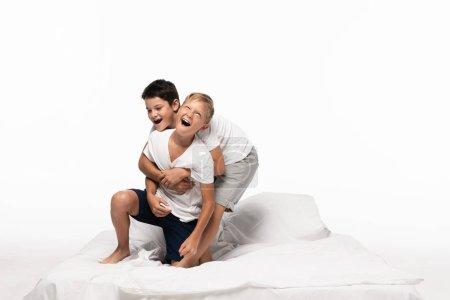 Photo pour Garçons gais imitant combats tout en s'amusant sur le lit isolé sur blanc - image libre de droit